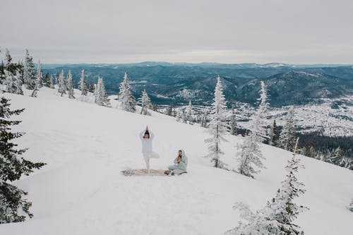 A Couple Meditating in the Snow Covered Mountain