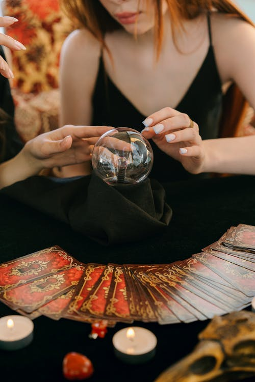 Crop unrecognizable female fortune tellers reading future with magical crystal ball and tarot cards during spiritual session