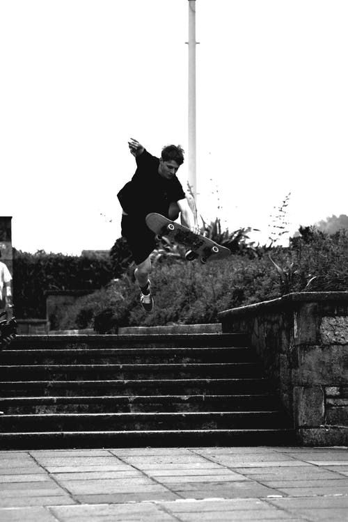 Grayscale Photo of Man Doing Trick on Skateboard on Park