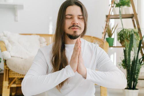 Peaceful male meditating with namaste gesture in apartment