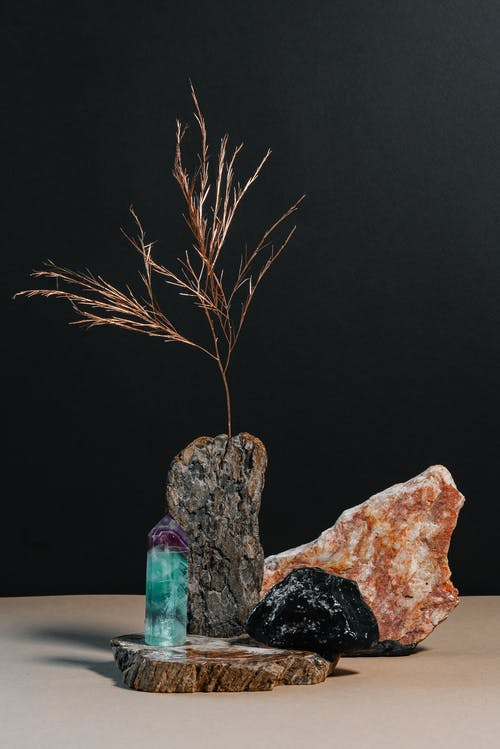 Composition of natural hard stones with dried branch of plant placed on table against black background