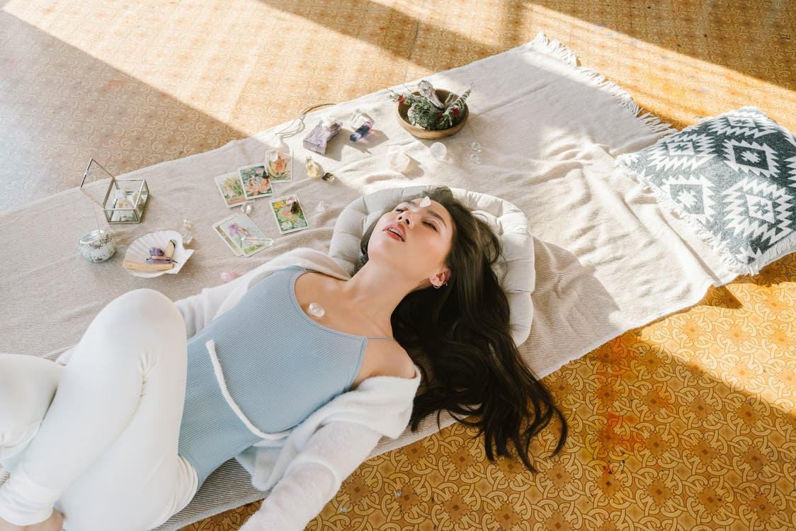 Serene Asian woman lying with chakra stone on chest