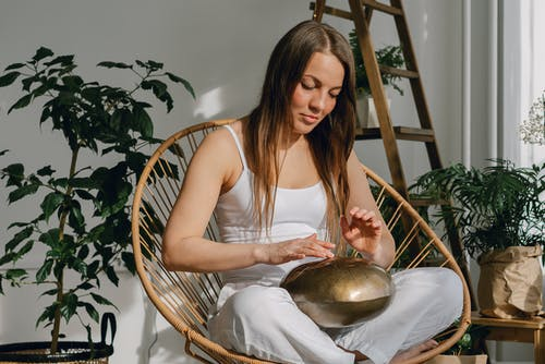 Young woman playing on steel tongue drum