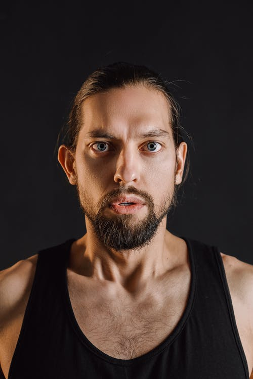 Scared man with beard against black background
