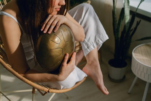 High angle of barefoot crop peaceful female embracing steel tongue drum instrument for meditation