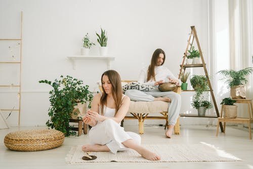 Full body of peaceful couple practicing meditation with palo santo stick and steel tongue drum in stylish apartment
