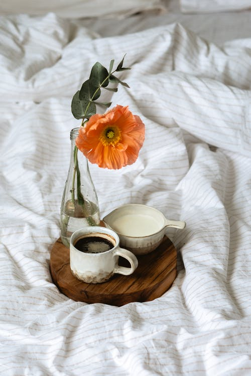 High angle of cup of aromatic coffee and milk jug placed on round wooden tray with vase of delicate fresh flower on soft bed in sunny morning