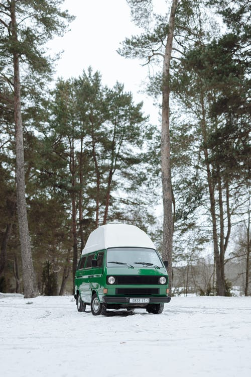 Green Van on Snow Covered Ground Near Trees