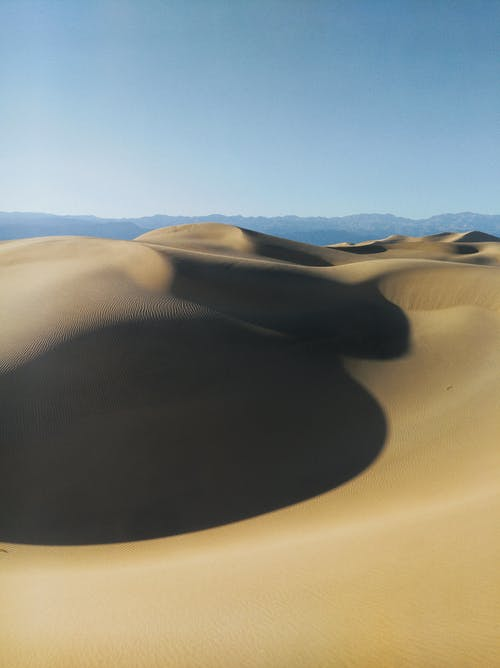 Black and White Hat on Brown Sand