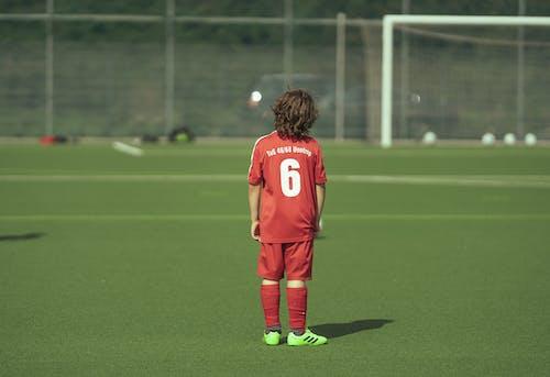 Faceless teenage boy football player standing on field