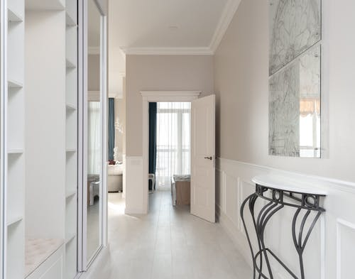 Hallway with empty opened wardrobe and mirror against wall with decorated white shelf in contemporary spacious light flat with rooms