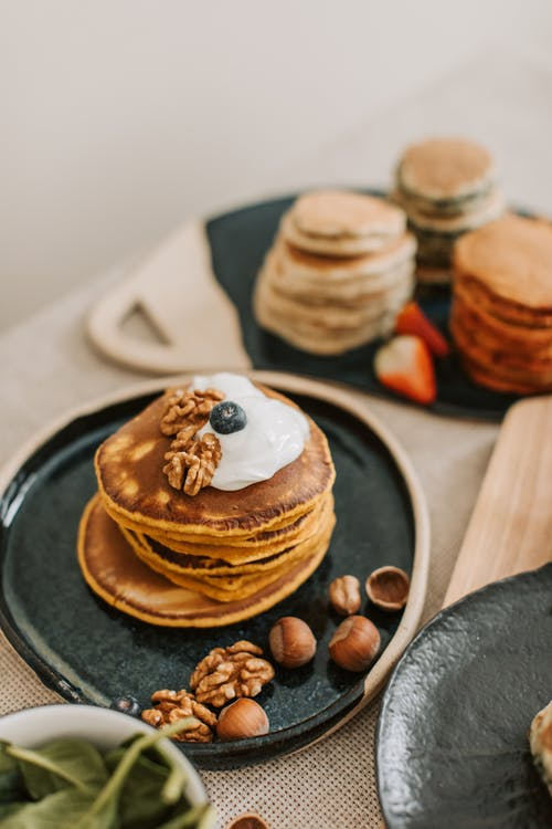 Close-Up Shot of Stack of Pancakes with Nuts on Top
