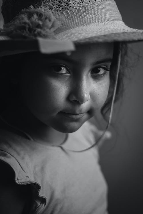 Grayscale Photo of a Smiling Girl Looking at Camera