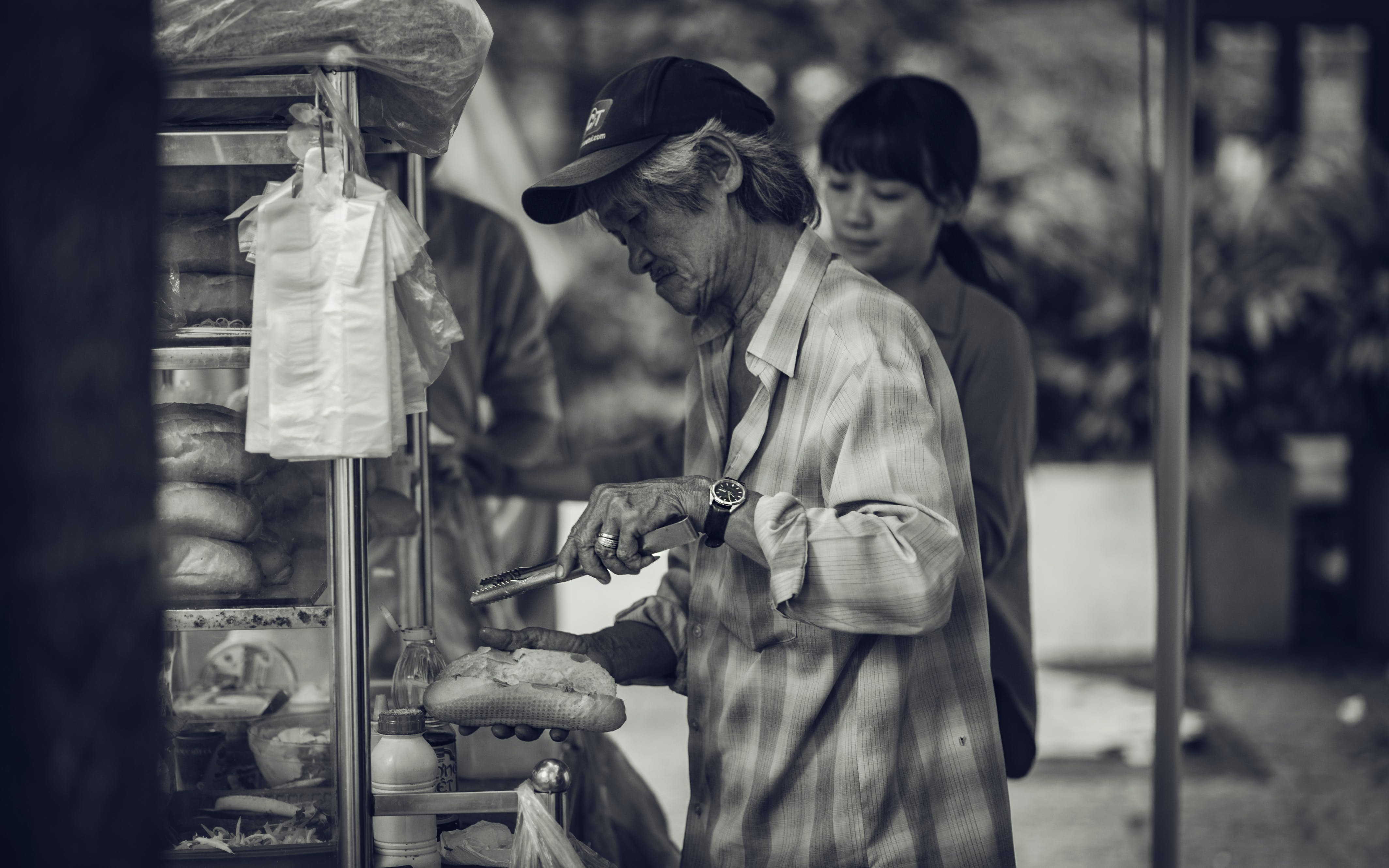 Man in Cap Holding a Pastry and Tong