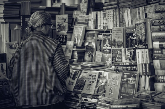 Person Standing in Front of Assorted Books in Gray Scale Photography