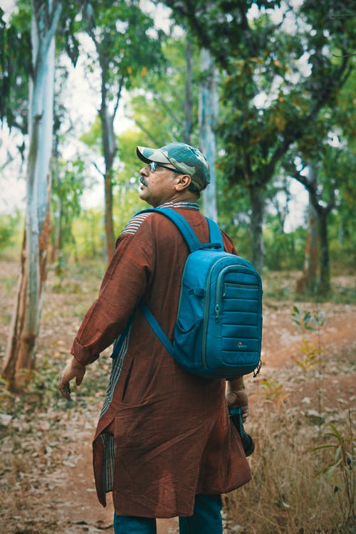 Man with Blue Backpack Walking into the Woods