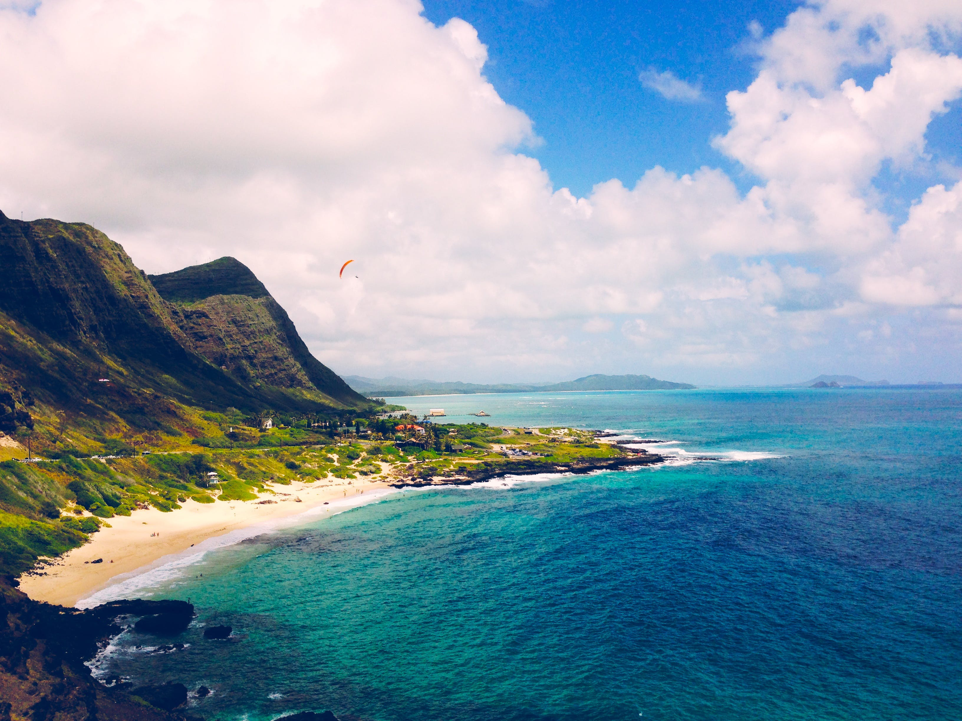 Green Mountains by the Shore Under White Clouds and Blue Sky