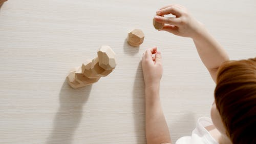 A Kid Playing Wooden Toys