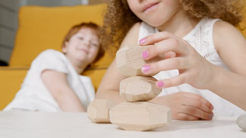 Close-Up Shot of a Girl Playing Wooden Toys