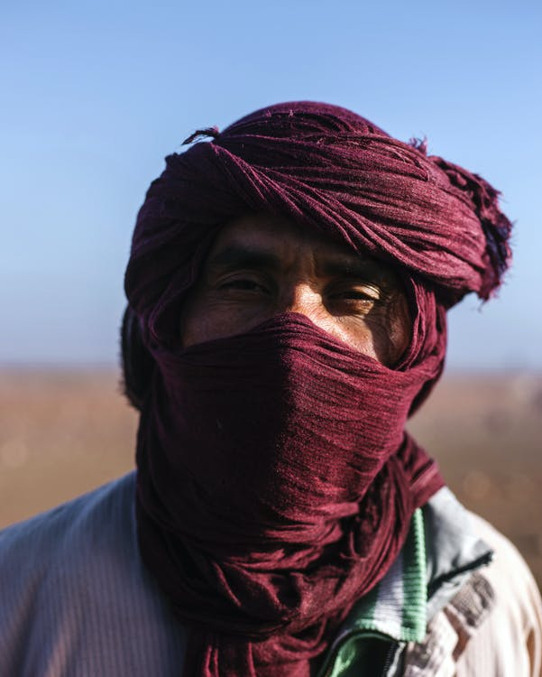 Ethnic man in traditional headscarf in desert