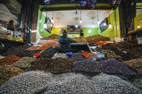 From below of African American man standing between market stalls with multi colored dried fruits and nuts illuminate with light bulbs