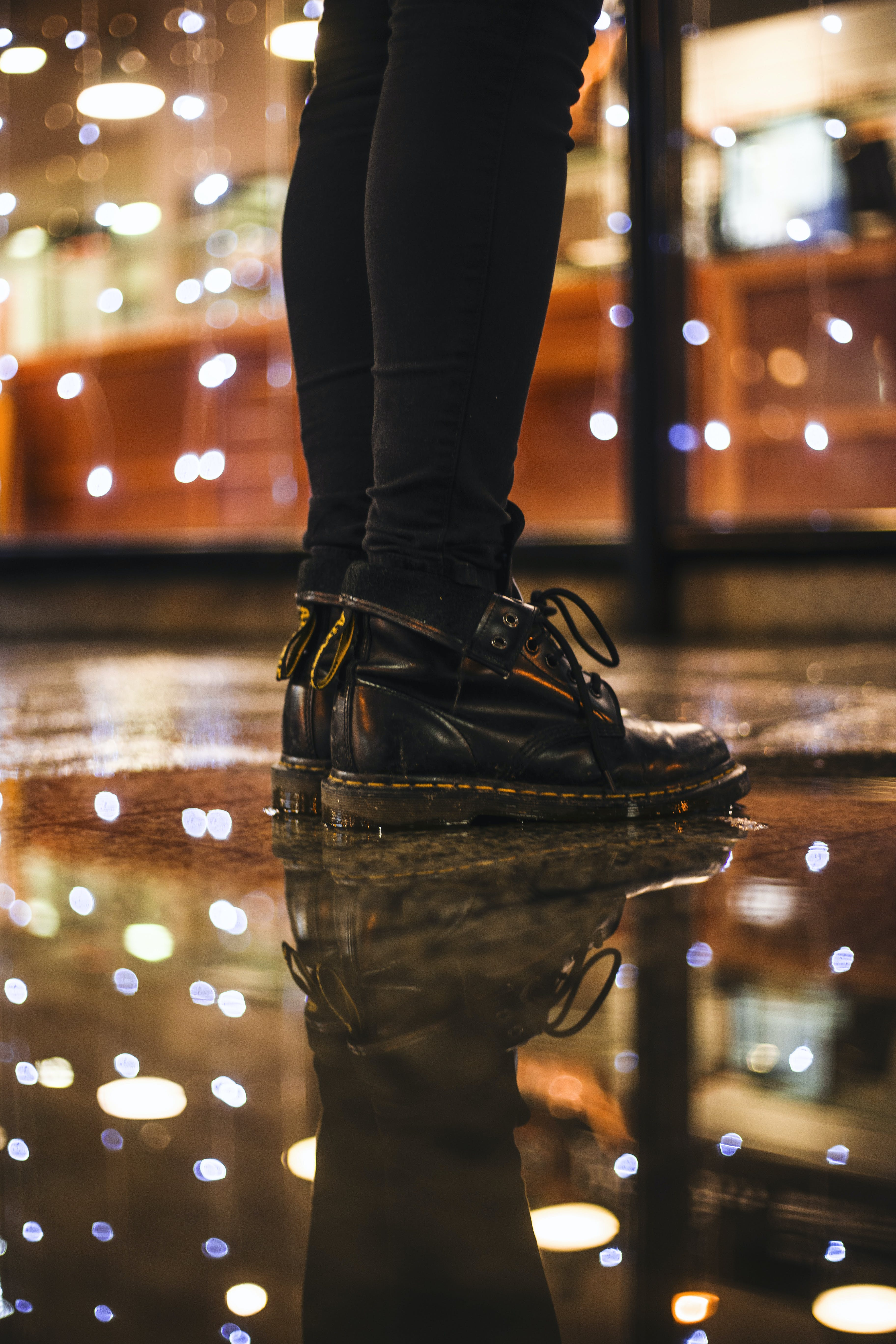 Photo of Person Wearing Black Fitted Jeans and Black Dr.martens Boots Standing on Black Floor Tiles