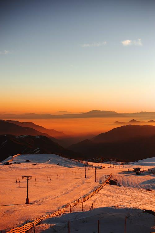 Snowy valley near mountains on sunset