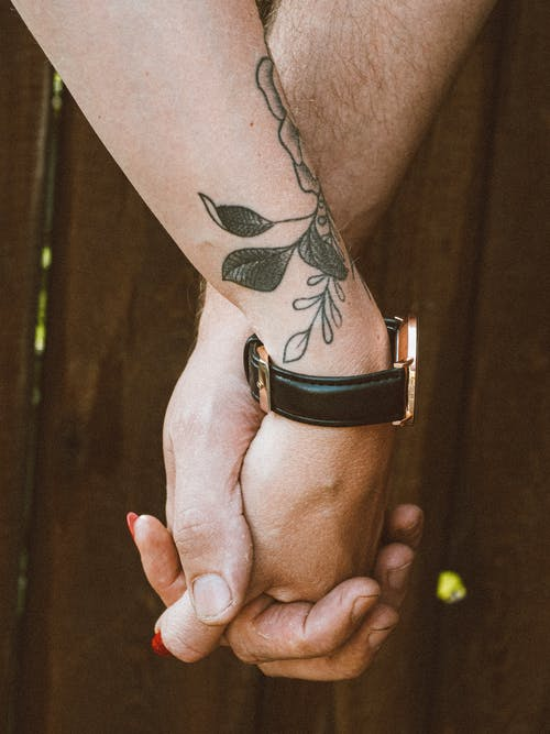 Crop anonymous loving young tattooed woman and man holding hands while standing against wooden fence in nature