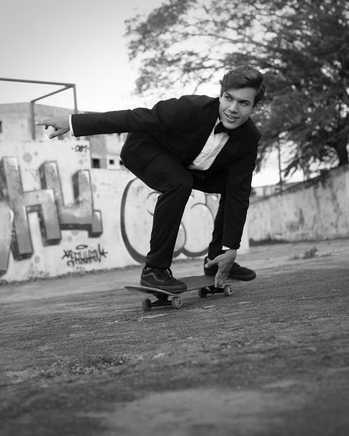 Black and white of positive young male millennial in elegant suit with bow tie smiling while riding skateboard in shabby park near graffiti walls