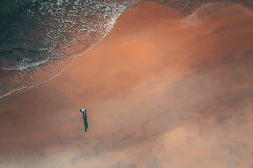 Faceless tourist admiring foamy sea from sandy beach