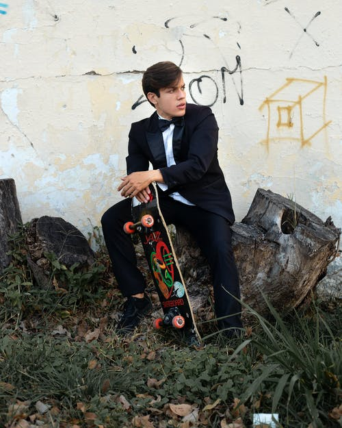 Stylish guy in classy suit sitting on log with skateboard in hand