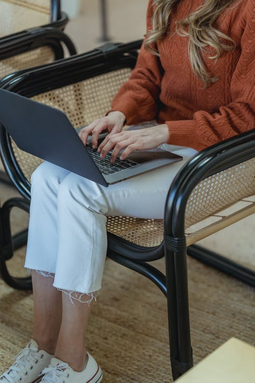 High angle of crop unrecognizable female remote employee sitting in armchair and typing on netbook while working online on startup