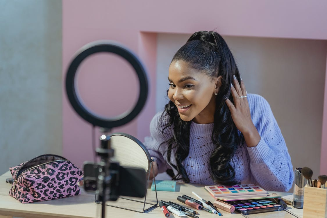 Positive African American female blogger touching hair while doing makeup and shooting video on cellphone on light ring