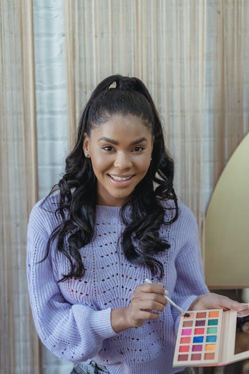 Smiling black woman taking eyeshadow with brush
