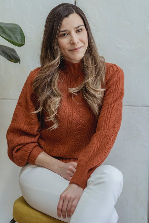 Charming female in sweater and skinny pants sitting on pouf with crossed legs and looking at camera