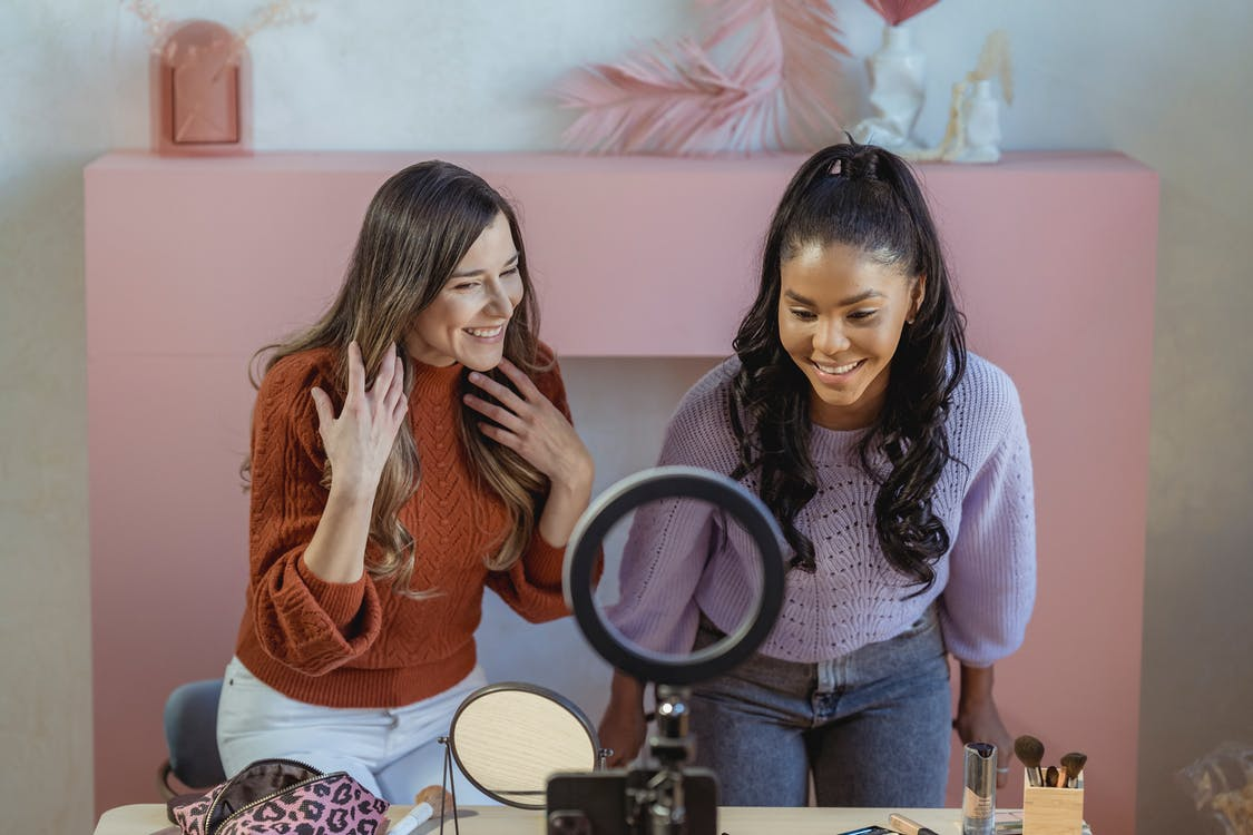 Positive multiethnic female makeup artists at table with professional supplies looking at smartphone near ring lamp while recording online lesson