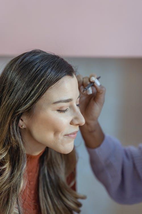 Crop makeup artist applying makeup on eyebrow of client