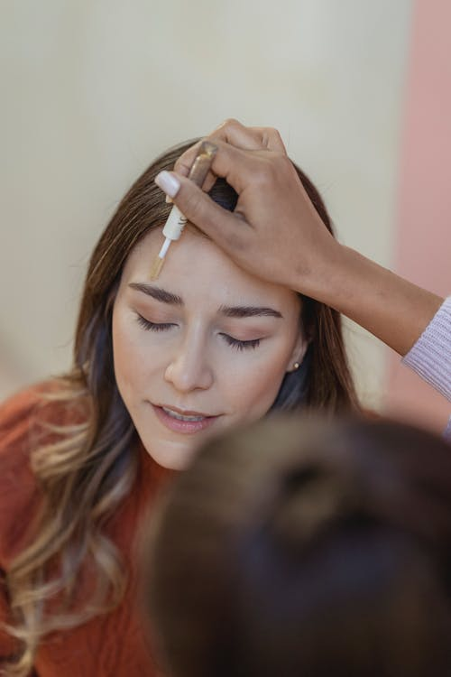 From above of crop anonymous cosmetologist applying corrector on face of female client in beauty salon