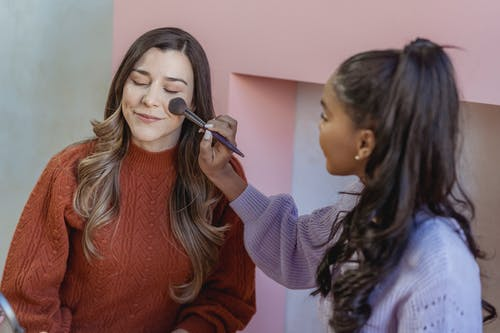 Young ethnic lady applying foundation on face of friend with brush