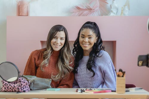 Diverse glad friends with long hair smiling and looking at camera in modern fashion studio