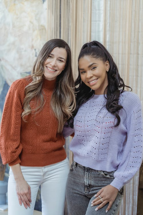 Multiracial cheerful friends with wavy hair in casual sweaters smiling and looking at camera