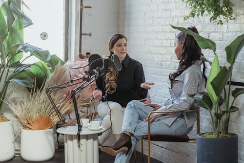 Multiracial trendy women chatting during podcast in studio