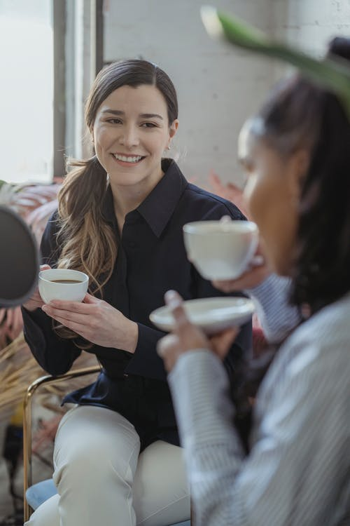 Cheerful diverse best friends drinking coffee together