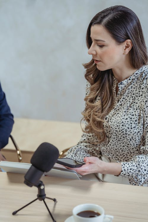 Crop focused female with long wavy hair talking about business at table with microphone in office