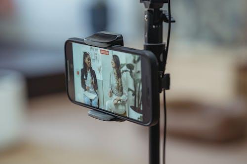 Modern smartphone on tripod recording video of content stylish women having friendly conversation
