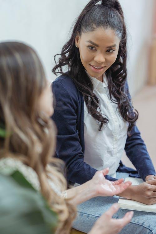 Black woman listening friend explaining details about work