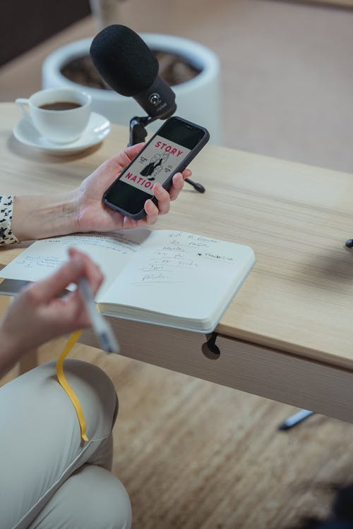 Crop unrecognizable woman using smartphone and writing in diary