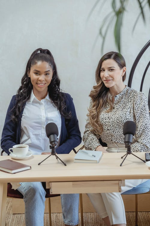 Content multiracial females wearing formal clothes sitting at desk with microphones during interview and looking at camera with smiles