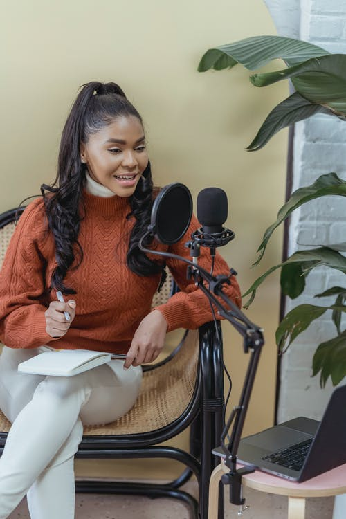 Smiling ethnic woman with microphone and laptop creating podcast in studio