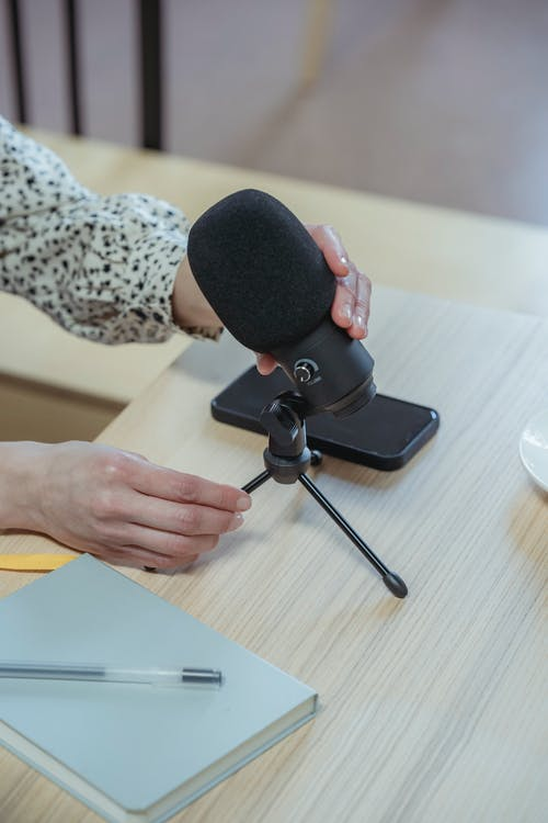 From above of crop unrecognizable female employee setting up microphone while sitting at wooden table with notebook and smartphone during briefing